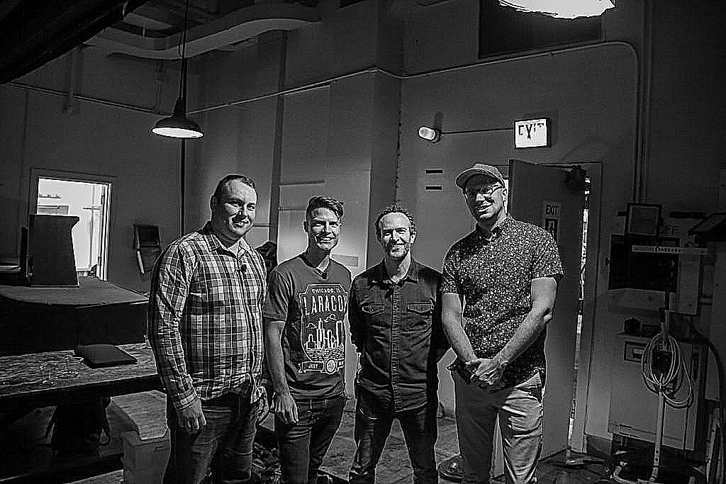 Adam Wathan, Justin Jackson, Jason Friend, and Taylor Otwell in a room backstage at Laracon 2018 in Chicaco.